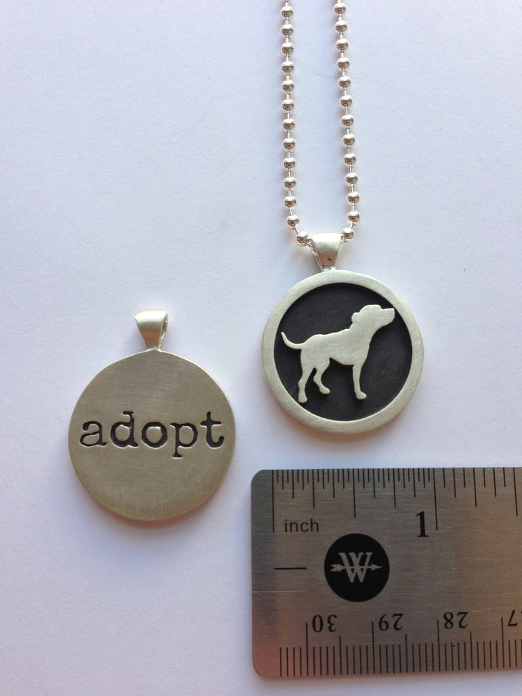 Image of girl's exclusive sterling silver tiny tim adopt necklace designed by gregg wolf