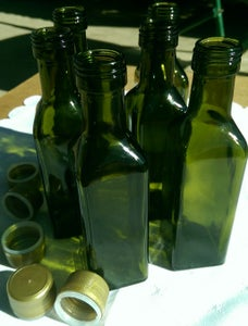 Image of Empty new 100 ml dark green glass olive oil bottles with gold lids.