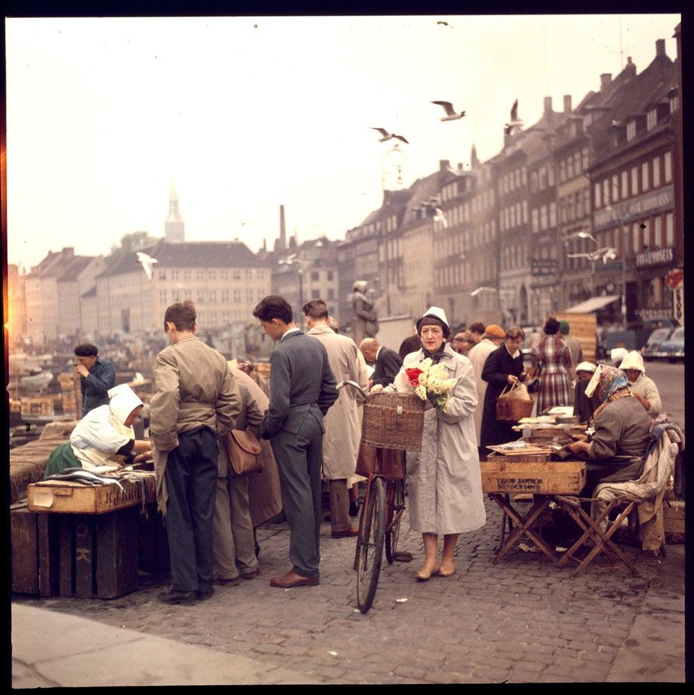 Image of A woman in postwar Denmark walking through an open air market