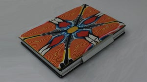 Image of Orange and yellow spiral polymer on leather and aluminum case (Rhyl Collection)