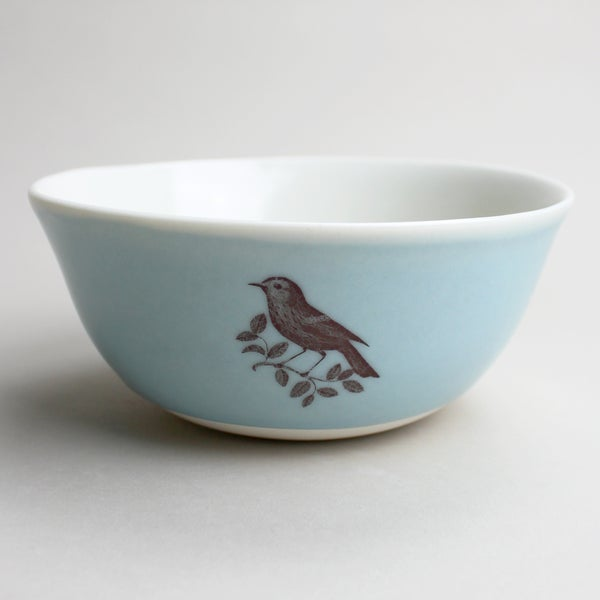 Image of rustic bowl with warbler, ocean