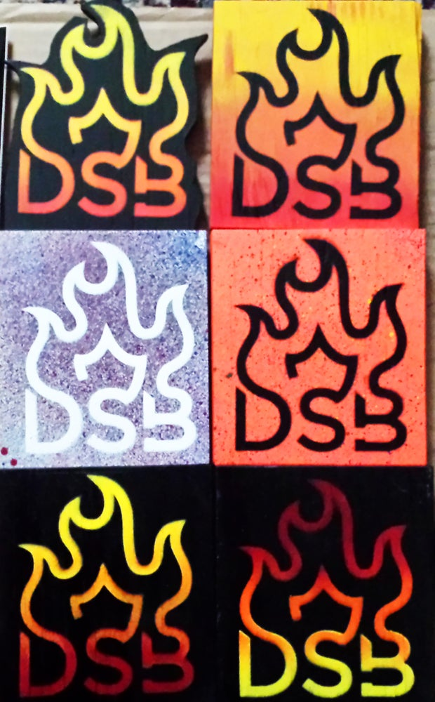 Image of DSB Products, including Wooden Flames, Sticker Packs and DSB Pendants
