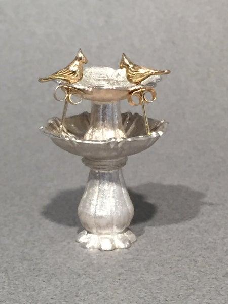 Image of 18K gold earrings on bird bath.