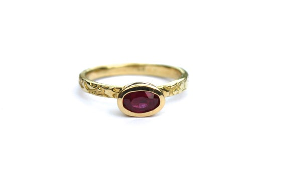 Image of oval ruby and 18k yellow gold tudor rose engagement ring