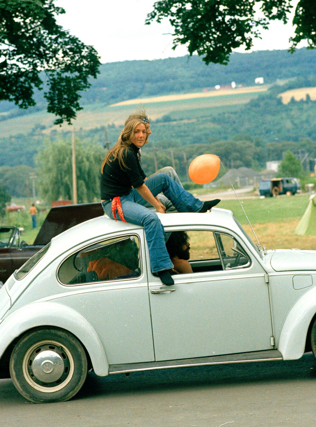 Image of Woman Catches A Ride Through A Rock Festival; Early 1970s