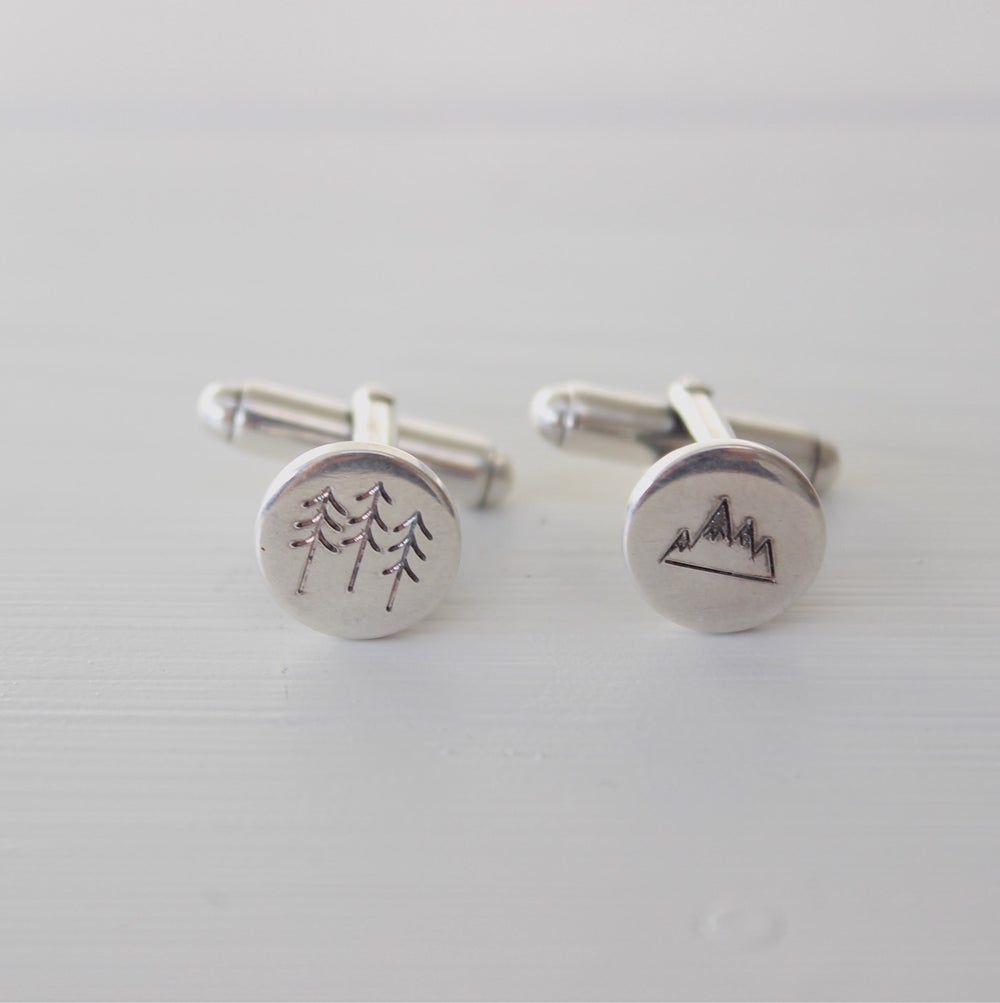 Image of cufflinks with snowy mountains and spruces