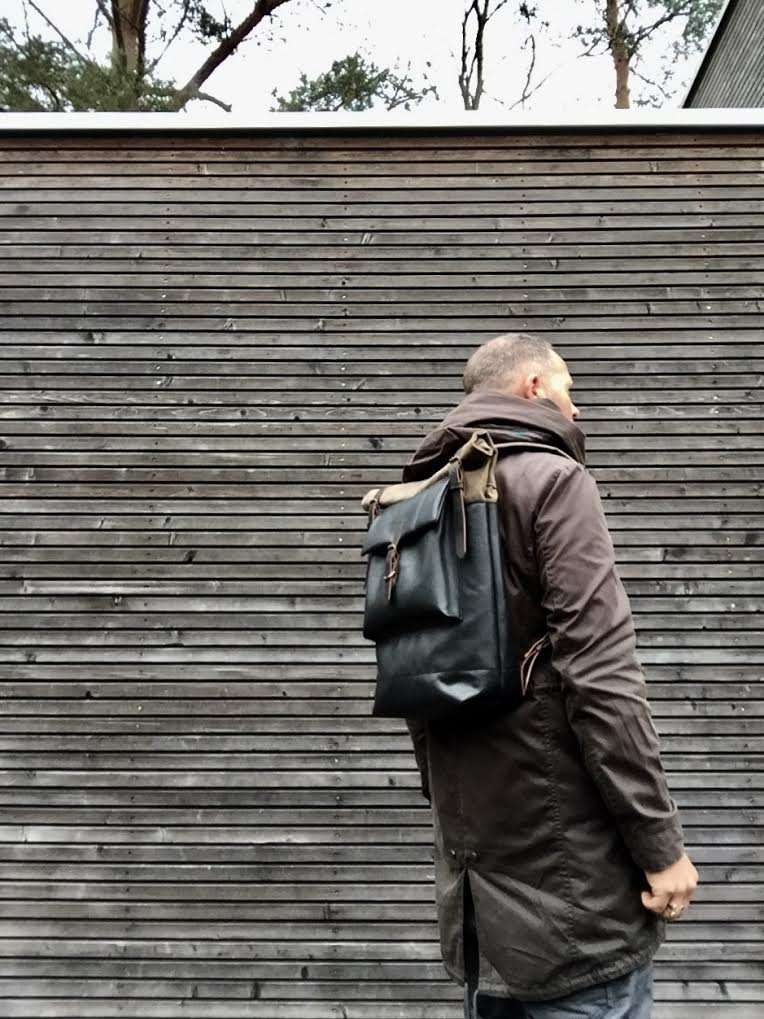 Image of Black leather backpack with waxed canvas roll to close top and leather front pocket
