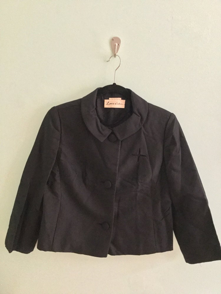 Image of black round collar jacket with large buttons
