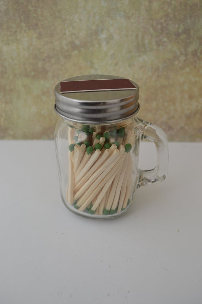Image of Mason jar with matches and strike on top strip