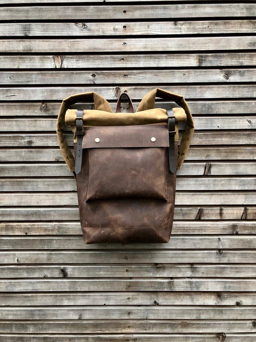 Image of Leather backpack with waxed canvas roll to close top and leather front pocket