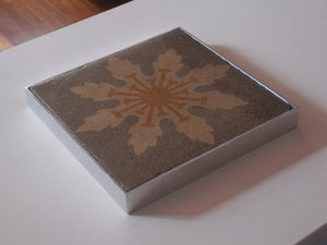 Image of Cream flower on grey trivet