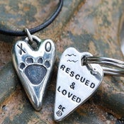 "Image of Heart shaped Dog Paw Pendant ""Rescued & Loved"" on the back"